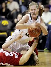 Iowa's Kelly Krei, top, fights for a loose ball with Wisconsin's Lindsay Smith during the first half of an NCAA college basketball game, Thursday, Jan. 19, 2012, in Iowa City, Iowa. Iowa won 69-57. (AP Photo/Cedar Rapids Gazette, Jim Slosiarek)