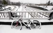 A snow-covered bicycle is locked to a bridge as unusually light traffic drives past below on Highway 520 near the University of Washington Thursday, Jan. 19, 2012, in Seattle. A monster Pacific Northwest storm coated the Seattle area in a thick layer of ice Thursday and brought much of the state to a standstill, sending hundreds of cars spinning out of control, temporarily shutting down the airport and knocking down so many trees that members of the Washington State Patrol brought chain saws to work. (AP Photo/Elaine Thompson)