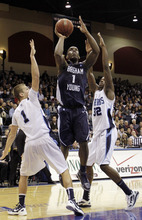 Brigham Young's Charles Abouo, center, shoots between San Diego's Johnny Dee, left, and Ken Rancifer in the first half during an NCAA college basketball game  Monday, Jan. 16, 2012, in San Diego. (AP Photo/Gregory Bull)