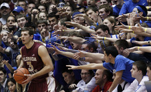 Duke fans reach for Florida State's Luke Loucks (3) as he in-bounds the ball against Duke during the second half of an NCAA college basketball game in Durham, N.C., Saturday, Jan. 21, 2012. Florida State won 76-73. (AP Photo/Gerry Broome)