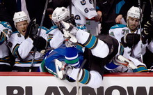 San Jose Sharks' Jamie McGinn, center right, checks Vancouver Canucks' Dan Hamhuis into the San Jose bench as Joe Pavelski, from left, Patrick Marleau and Benn Ferriero react during the second period of an NHL hockey game in Vancouver, British Columbia, Saturday, Jan. 21, 2012. (AP Photo/The Canadian Press, Darryl Dyck)