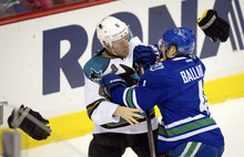 San Jose Sharks' Joe Pavelski (8) throws his gloves off as he fights with Vancouver Canucks' Keith Ballard during the second period of an NHL hockey game in Vancouver, British Columbia, Saturday, Jan. 21, 2012. The Canucks won 4-3. (AP Photo/The Canadian Press, Darryl Dyck)