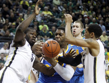 Oregon's Olu Ashaolu (5) and teammate Devoe Joseph, right, battle for a rebound with UCLA's Joshua Smith, center, as his teammate Travis Wear, rear, looks on in the first half of  an NCAA college basketball game Saturday, Jan. 21, 2012, in Eugene, Ore.  (AP Photo/Rick Bowmer)