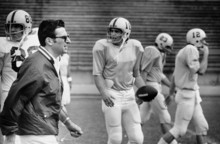 Joe Paterno, Penn State football coach, calls his Nittany Lions to a workout in Miami, Fla., Wednesday, Dec. 26, 1973.  The team arrived Christmas night and is working out daily to prepare for their Orange Bowl game with Louisiana State University (LSU) on Jan. 1.  Penn State players are Buddy Ellis (18), Walt Addie (23), and Tom Shuman (12).  (AP Photo)