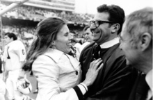 ** ADVANCE FOR WEEKEND EDITIONS, AUG. 29-30 **  FILE - In this Jan. 1, 1972 file photo, Penn State football coach Joe Paterno is embraced by his wife, Sue, following Penn State's 30-6 victory over Texas in the Cotton Bowl in Dallas.  Here's the story behind Joe Paterno's rolled-up pants: Back in the late 1960s, his wife, Sue, wanted the cuffs rolled up because mud would get on his then-wool slacks while he was coaching. Now that JoePa has turned to his trademark khakis, she's not worried anymore.   (AP Photo/File)