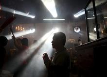 An Indonesian ethnic Chinese man prays during the Chinese Lunar New Year celebration at Dharma Bakti temple in Chinatown in Jakarta, Indonesia, Monday, Jan. 23, 2012. (AP Photo/Dita Alangkara)