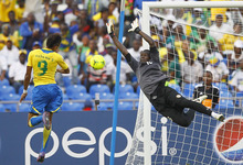 Gabon Pierre Eymerick Aubameyang , left, scores the first goal as  Niger goalkeeper Saminou Rabo tries to catch it during their African Cup of Nations Group C soccer match at Stade De L'Amitie in Libreville, Gabon, Monday, Jan. 23, 2012. (AP Photo/Francois Mori)