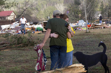 Russ Butler hugs his wife, Amber, as their friends and neighbors begin the cleanup process in Oak Grove, Ala., Monday, Jan. 23, 2012. At least one person was killed when a suspected tornado swept through the area overnight.  (AP Photo/Dave Martin)