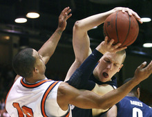 BYU's Nate Austin, right, battles for the ball with Pepperdines's Joshua Lowery, left, during the first half of an NCAA college basketball game, Saturday, Jan. 21, 2012, in Moraga, Calif. (AP Photo/Ringo H.W. Chiu)