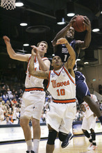 BYU's Charles Abouo, top, battles for a rebound against Pepperdine's Corbin Moore (44) and Joshua Lowery (10) during the second half of an NCAA college basketball game, Saturday, Jan. 21, 2012, in Moraga, Calif. BYU won 77-64. (AP Photo/Ringo H.W. Chiu)