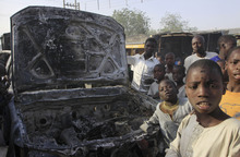 CORRECTS SPELLING OF NEIGHBORHOOD TO SHEKA    Children gather around a burntout police truck following an overnight attack at Sheka Police station in Kano, Nigeria, on Wednesday, Jan. 25, 2012. Suspected members of a radical Islamist sect attacked a police station overnight in the north Nigeria city where its previous coordinated assault killed at least 185 people. Youths on Wednesday morning overran the police station in the Sheka neighborhood of Kano, a city of more than 9 million people.  (AP Photo/Sunday Alamba)