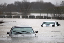 Flooded out cars sit in high water in Fort Worth, Texas on Wednesday, Jan.  25, 2012.   Rainstorms and strong winds across parts of Texas have left thousands of people without electricity and facing the threat of worse conditions. (AP Photo/The Dallas Morning News, Tom Fox)  MANDATORY CREDIT; MAGS OUT; TV OUT; INTERNET OUT