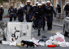 Riot police chase anti-government protesters Wednesday, Jan. 25, 2012, in Manama, Bahrain. Security forces in Bahrain have fired tear gas and stun grenade after opposition groups staged a rare march into the center of the capital Manama. (AP Photo/Hasan Jamali)