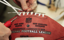 Aaron Plummer laces an official game ball for the NFL football Super Bowl XLVI at Wilson Sporting Goods Co.  in Ada, Ohio, Monday, Jan. 23, 2012. The New England Patriots will play the New York Giants in the Super Bowl on Feb. 5 in Indianapolis. (AP Photo/Tony Dejak)