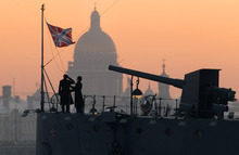 Naval cadets lower the flag of the navy cruiser Aurora at a daily ceremony near the front deck gun in St.Petersburg, Russia, Thursday, Jan. 26, 2012, with the St. Isaak's Cathedral seen on the background. On the night of Oct. 25-26, 1917, crew members on the Aurora used the front deck gun to fire a blank shot at the Winter Palace, then the residence of the Provisional Government, giving the signal to leftists to storm the palace and to begin the October Revolution. (AP Photo/Dmitry Lovetsky)