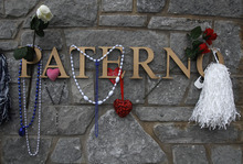 Mementos including flowers, beads and pom poms hang from former Penn State football coach Joe Paterno's name near his statue in front of Beaver Stadium in State College, Pa. Thursday Jan. 26, 2012.  A capacity crowd of more than 12,000 is expected to pack Penn State's Bryce Jordan Center  for one more tribute to  Paterno, the Hall of Fame football coach who died Sunday from lung cancer. (AP Photo/Jacqueline Larma)