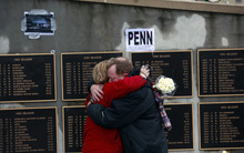 Laura Kunig hugs Bill Weaver as they meet near the statue of former Penn State football coach Joe Paterno in front of Beaver Stadium in State College, Pa. Thursday Jan. 26, 2012.  Both Kunig and Weaver are Penn State graduates and are active in Penn State alumni activities in Pittsburgh. A capacity crowd of more than 12,000 is expected to pack Penn State's Bryce Jordan Center  for one more tribute to Paterno, the Hall of Fame football coach who died Sunday from lung cancer.  (AP Photo/Jacqueline Larma)