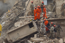 Rescue workers carry the body of a victim after a building collapsed in Rio de Janeiro, Brazil, Thursday Jan. 26, 2012. A multistory building collapsed in Rio's center Wednesday evening, leaving rubble strewn over a wide area but confusion about the number of possible victims and the cause. (AP Photo/Felipe Dana)