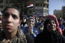 An Egyptian protestor, center, reacts while listening to another woman, not pictured, telling a story about her son who is jailed in an Egyptian prison, during a rally to mark the first anniversary of