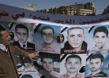 An Egyptian protesot, left, point at a banner showing pictures of people killed in clashes with security forces, during a rally to mark the first anniversary of