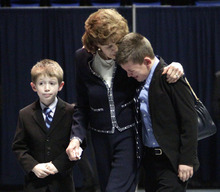 Sue Paterno, center, wife of former Penn State football coach Joe Paterno, consoles her grandson as they leave a memorial service for Joe at Penn State's Bryce Jordan Center in State College, Pa., Thursday Jan. 26, 2012. A capacity crowd of more than 12,000 packed the Bryce Jordan Center for one more tribute to Paterno, the Hall of Fame football coach who died Sunday from lung cancer.  (AP Photo/Gene J. Puskar)