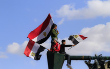Egyptians protesters wave the national flag from their perch atop a lamp post at a rally to mark the first anniversary of the