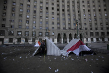 An Egyptian protestor camping in Tahrir Square, walks out of a tent toward a rally marking the first anniversary of