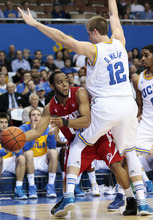 Utah guard Chris Hines, left, looks to pass as UCLA's David Wear (12) and Lazeric Jones defend in the first half of an NCAA college basketball game, Thursday, Jan. 26, 2012, in Los Angeles. (AP Photo/Jason Redmond)