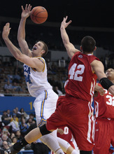 UCLA forward Travis Wear, left, shoots the ball as Utah's Jason Washburn (42) and George Matthews defend in the second half of an NCAA college basketball game Thursday, Jan. 26, 2012, in Los Angeles. UCLA won 76-49. (AP Photo/Jason Redmond)