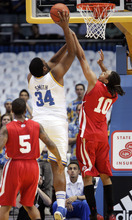 UCLA center Joshua Smith (34) shoots as Utah's Dijon Farr (10) and Kareem Storey (5) defend in the first half of an NCAA college basketball game, Thursday, Jan. 26, 2012, in Los Angeles. (AP Photo/Jason Redmond)