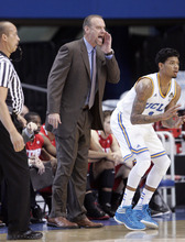 Utah head coach Larry Krystkowiak, center, yells to his players as UCLA guard Tyler Lamb, right, looks on in the first half of an NCAA college basketball game Thursday, Jan. 26, 2012, in Los Angeles. (AP Photo/Jason Redmond)