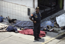 A police officer stands next to a group of bodies outside the