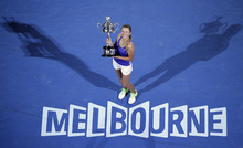 Victoria Azarenka of Belarus holds her trophy aloft after defeating Russia's Maria Sharapova to win the women's singles final at the Australian Open tennis championship, in Melbourne, Australia, Saturday, Jan. 28, 2012. (AP Photo/John Donegan)