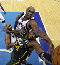 Dallas Mavericks' Lamar Odom, top, reaches over Utah Jazz's Paul Millsap (24) while competing for a rebound as  Mavericks' Vince Carter, below, looks on in the second half of an NBA basketball game on Friday, Jan. 27, 2012, in Dallas. The Mavericks won 116-101. (AP Photo/Tony Gutierrez)