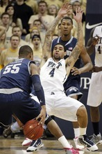 Georgetown's Jabril Trawick (55) takes the ball between his legs as Pittsburgh's John Johnson (4) defends in the first half of the NCAA college basketball game on Saturday, Jan. 28, 2012, in Pittsburgh. (AP Photo/Keith Srakocic)