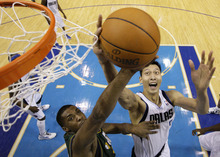 Dallas Mavericks' Yi Jianlian, right, of China, fights for a rebound against Utah Jazz's Derrick Favors, front left, in the second half of an NBA basketball game on Friday, Jan. 27, 2012, in Dallas. The Mavericks won 116-101. (AP Photo/Tony Gutierrez)