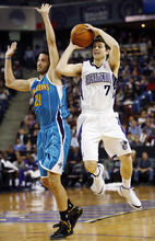 Sacramento Kings guard Jimmer Fredette (7) shoots against New Orleans Hornets' Greivis Ayon (21) during the second half of an NBA basketball game in Sacramento, Calif., Sunday, Jan. 1, 2012. The Kings won 96-80. (AP Photo/Steve Yeater)