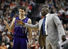 Sacramento Kings head coach Keith Smart talks with Jimmer Fredette (7) in the first quarter during an NBA basketball game with the Portland Trail Blazers Monday, Jan. 23, 2012, in Portland, Ore.  (AP Photo/Rick Bowmer)