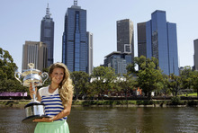 Victoria Azarenka of Belarus poses with her trophy on the banks of the Yarra River following her win over Russia's Maria Sharapova in the women's singles final at the Australian Open tennis championship, in Melbourne, Australia, Sunday, Jan. 29, 2012. (AP Photo/Mark Baker)