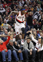 Portland Trail Blazers' Gerald Wallace (3) jumps out of the crowd after chasing loose ball in the third quarter of an NBA basketball game against Phoenix Suns Friday, Jan. 27, 2012, in Portland, Ore. (AP Photo/Rick Bowmer)