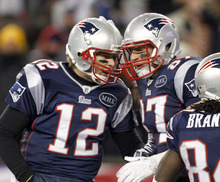 New England Patriots tight end Rob Gronkowski (87) is congratulated by quarterback Tom Brady (12) after catching a 10-yard touch pass against the Denver Broncos during the first half of an NFL divisional playoff football game Saturday, Jan. 14, 2012, in Foxborough, Mass. (AP Photo/Elise Amendola)
