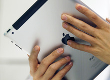 A customer checks on his new Apple Inc.'s iPad 2 tablet computer at a shop in Hong Kong Friday, April 29, 2011. (AP Photo/Kin Cheung)