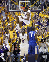LSU forward Storm Warren (24) hangs from the rim after dunking the ball against Kentucky during the first half of an NCAA college basketball game in Baton Rouge, La., Saturday, Jan. 28, 2012. (AP Photo/Gerald Herbert)