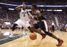 Portland Trail Blazers forward Gerald Wallace (3) drives past Utah Jazz forward Josh Howard (8) during the first half of an NBA basketball game Monday, Jan. 30, 2012, in Salt Lake City. (AP Photo/Jim Urquhart)