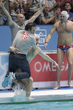 A player throws coach Dejan Udovicic of Serbia in the water as the team celebrates winning the gold defeating Montenegro with 9-8 in the men's final match of the European Championships Waterpolo at Pieter van den Hoogenband swim stadium in Eindhoven, south central Netherlands, Sunday Jan. 29, 2012. (AP Photo/Peter Dejong)