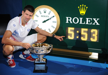 Serbia's Novak Djokovic poses for a photo of a clock showing the match time of his final against Spain's Rafael Nadal during the men's singles final at the Australian Open tennis championship, in Melbourne, Australia, early Monday, Jan. 30, 2012. (AP Photo/Theo Karanikos)