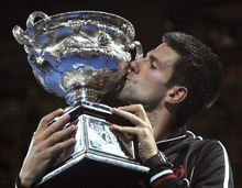 Novak Djokovic of Serbia kisses the trophy during the awarding ceremony after defeating Rafael Nadal of Spain  in the men's singles final at the Australian Open tennis championship, in Melbourne, Australia, early Monday, Jan. 30, 2012.  (AP Photo/Andrew Brownbill)