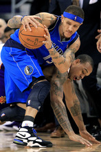 Dallas Mavericks' Delonte West, left, comes up with the ball after battling Phoenix Suns' Shannon Brown during the third quarter in an NBA basketball game, Monday, Jan. 30, 2012, in Phoenix. The Mavericks won 122-99. (AP Photo/Ross D. Franklin)