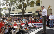 Republican presidential candidate, former Massachusetts Gov. Mitt Romney, campaigns at Sugden Plaza in Naples, Fla., Sunday, Jan. 29, 2012. At rear is Rep. Mary Bono Mack, R-Calif., and Rep. Connie Mack, R-Fla. (AP Photo/Charles Dharapak)