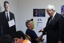 Republican presidential candidate, former House Speaker Newt Gingrich meets with campaign workers in view of a cutout of former President Ronald Reagan during a visit to the  Polk County campaign office, Tuesday, Jan. 31, 2012, in Lakeland, Fla. (AP Photo/Matt Rourke)